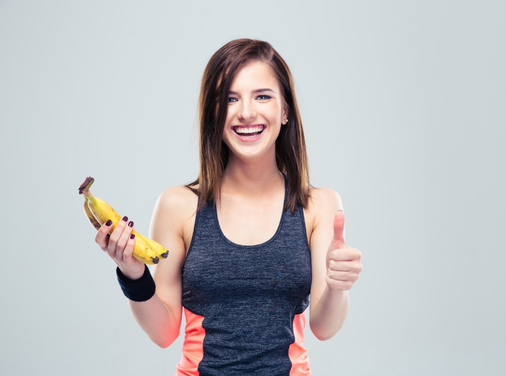 Laughing fitness woman holding banana and showing thumb up over gray background. Looking at camera